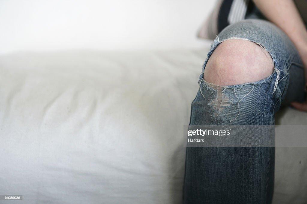 Knee protruding through jeans : Stock Photo