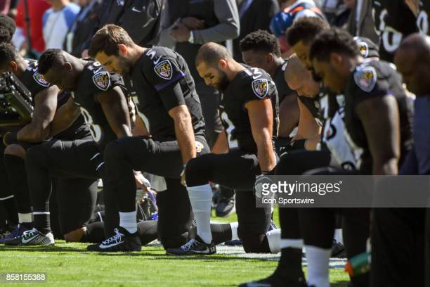 Kneeling are Baltimore Ravens wide receiver Chris Moore quarterback Joe Flacco and wide receiver Michael Campanaro prior to the National Anthem on...
