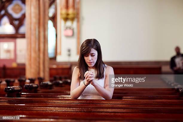 kneeling caucasian woman praying in church pew - mulher orando de joelhos imagens e fotografias de stock