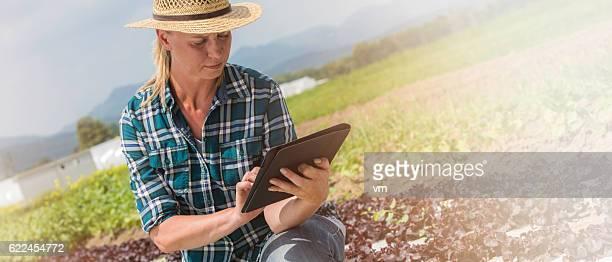 Kneeling female farmer with digital tablet