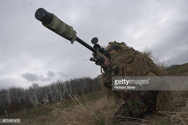 Kneeling in undergrowth a camouflaged British infantry soldier is seen looking down the telescopic sight of the new Britishmade Long Range L115A3...