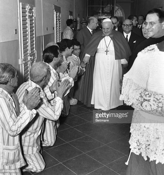 Kneeling prisoners applaud as Pope John XXIII visits the Regina Coeli Prison, Rome's largest, Dec. 26th. The Pontiff spent an hour and ten minutes...