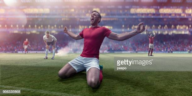 Kneeling Professional Soccer Player Shouting With Arms Out In Celebration