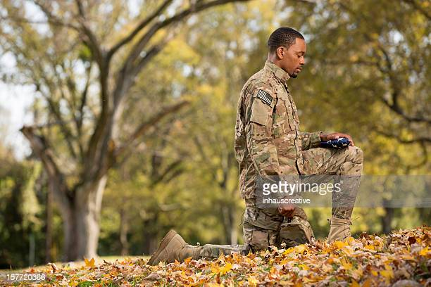 kneeling soldier praying over an american flag - soldier praying stock photos and pictures
