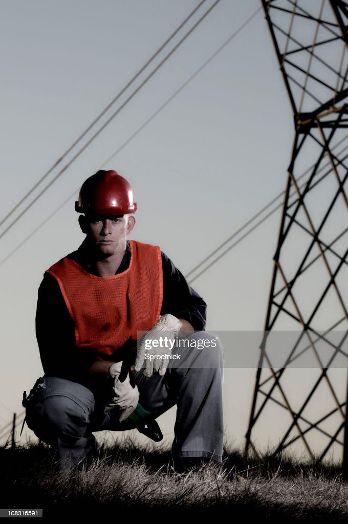 Kneeling utility worker against power lines : Stock Photo