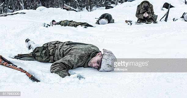 kneeling wwii soldier praying for dead buddy war casualties - dead soldier stock photos and pictures