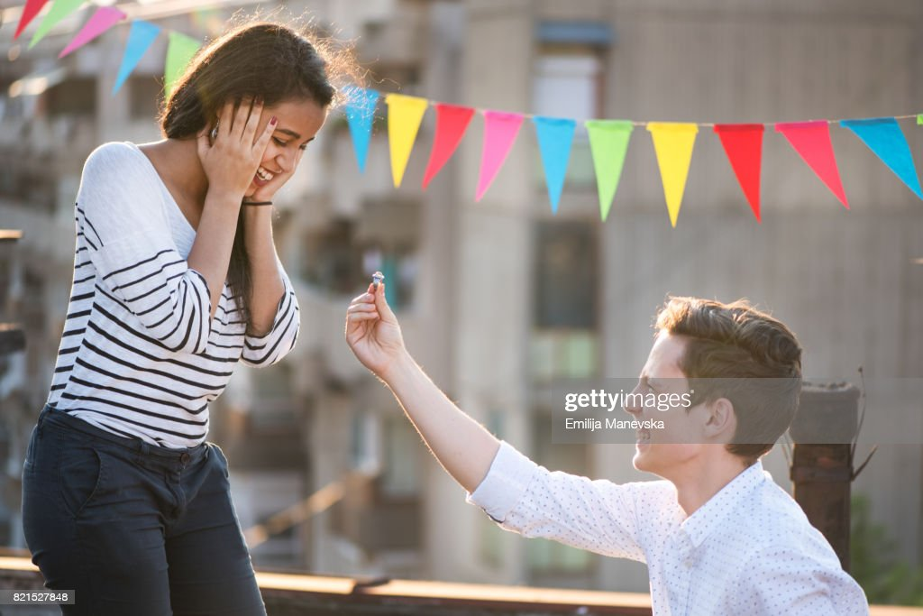 Kneeling young man proposing to his girlfriend : Stock Photo