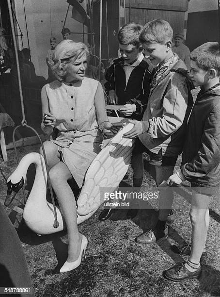 Knef Hildegard actress singer Germany * Hildegard Knef sitting on a carousel swan gives out autographs to some children at the First GermanAmerican...