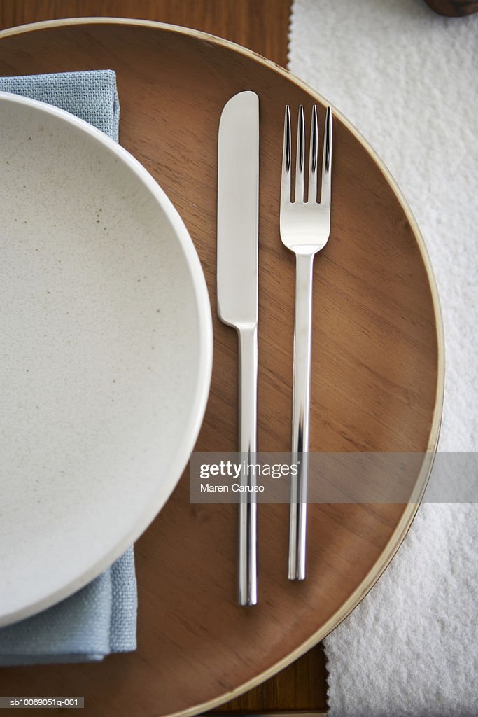 Knife and fork on wooden plate, view from above, close-up : Stockfoto