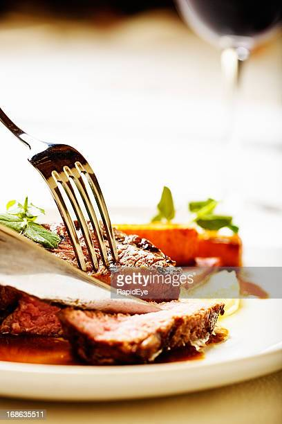 Knife and fork slice juicy steak, red wine in background