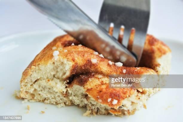 knife and fork slicing a tasty fresh cinnamon roll - rafael ben ari bildbanksfoton och bilder