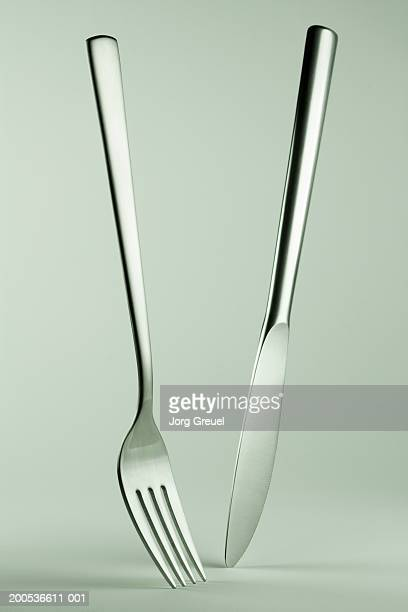 knife and fork standing on tips, close-up - forchetta foto e immagini stock