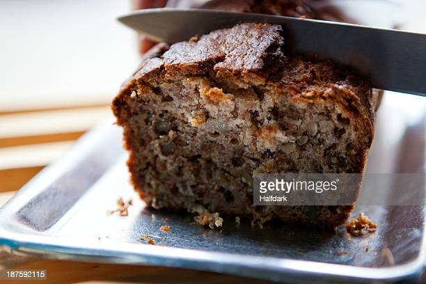 a knife cutting into a loaf of banana bread in a cafe - banana loaf stockfoto's en -beelden