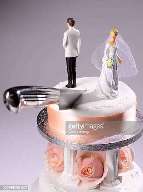 Knife cutting wedding cake between bride and groom