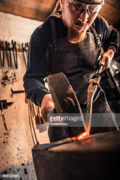 Knife Maker Shaping Hot Piece Of Iron With Hammer On Anvil