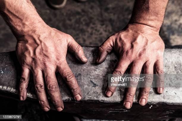 knife maker with soot-blackened hands on anvil - kunsthandwerker stock-fotos und bilder