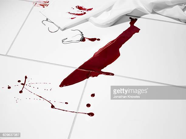 Knife shaped blood stain on a white tiled floor.