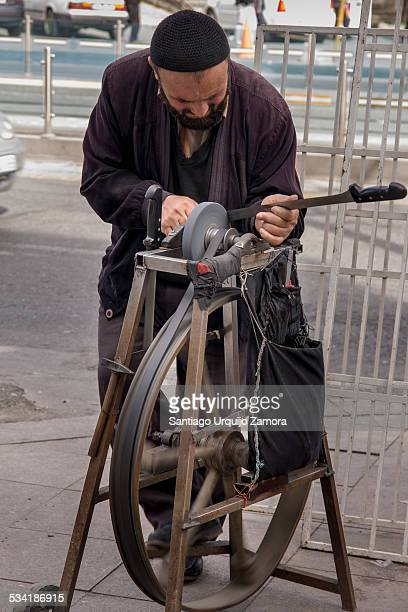 Knife sharpener sharpening a knife with a sharpening machine in a street of Istanbul, Marmara, Turkey