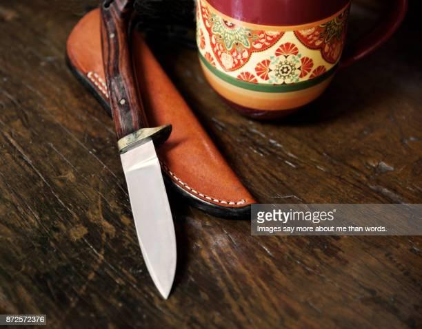 Knife, sheath, mug on wooden board. Still life.