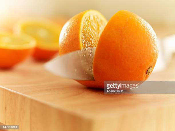 Knife slicing orange on cutting board