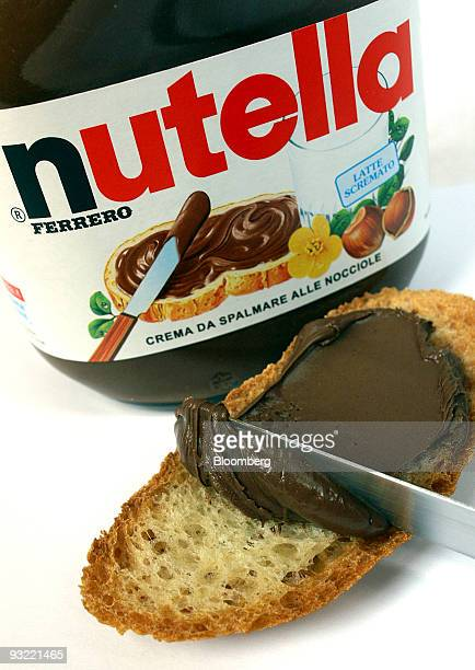 A knife spreads Fererro SpA's Nutella chocolatehazelnut spread onto a piece of bread in Milan Italy on Thursday Nov 19 2009 Michele Ferrero sold his...