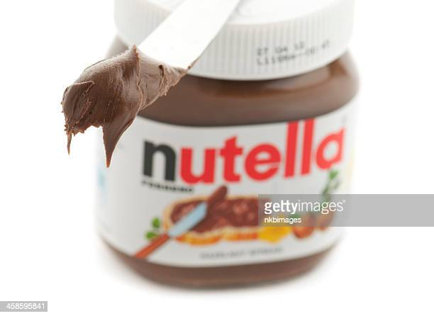 Knife with Nutella in front of jar