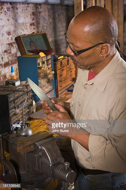 Knifemaker inspecting a blade