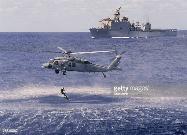 mh-60s knight hawk helicopter recovering swimmer - helicopter stock pictures, royalty-free photos & images
