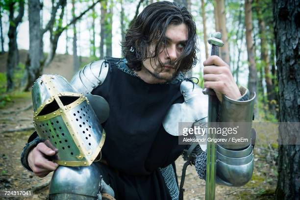 Knight Holding Sword And Helmet In Forest