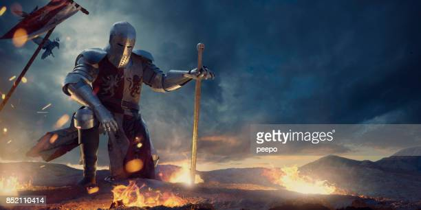 knight in amour kneeling with sword on hilltop near fire - warrior person stock photos and pictures