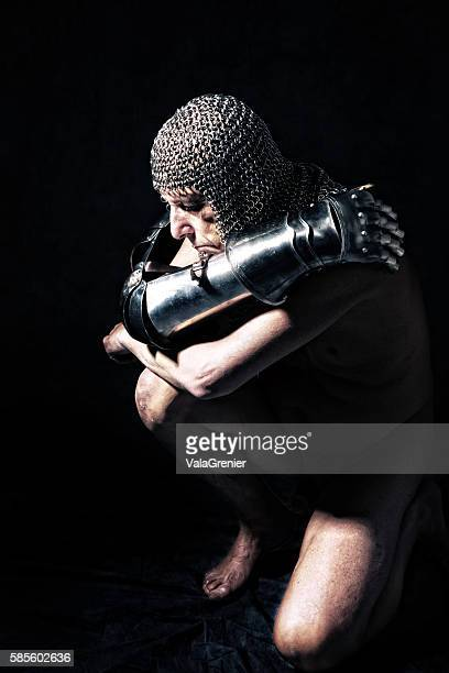 Knight in partial armour kneeling with arms around self.