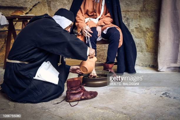 Knight of the Knights Hospitallers washing aHoly Land pilgrim's feet, 13th century. Historical reenactment in Malta.