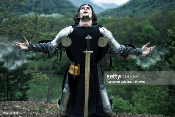Knight With Arms Outstretched While Praying In Forest
