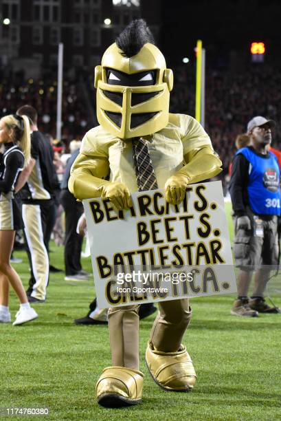 Knightro the UCF mascot with a Bearcats Beats Battlestar Galactica poster while dressed as Dwight Schrute from NBC's The Office during a college...