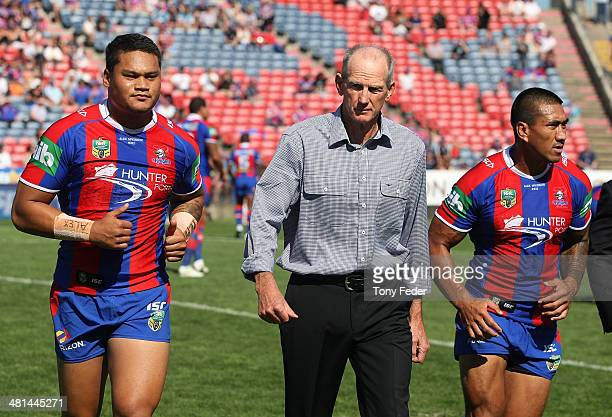 Knights coach Wayne Bennett walks off the ground with Knights players Joey Leilua and Dave Fa'alogo during the round four NRL match between the...