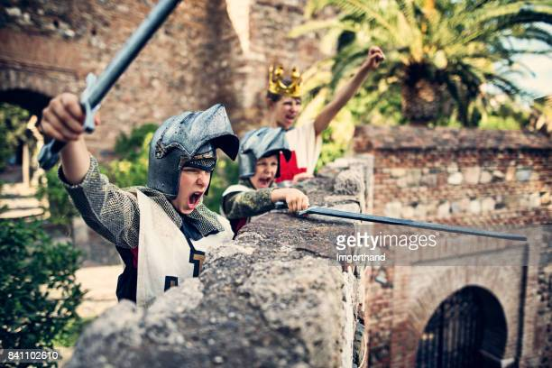 knights defending the castle - castle stock photos and pictures