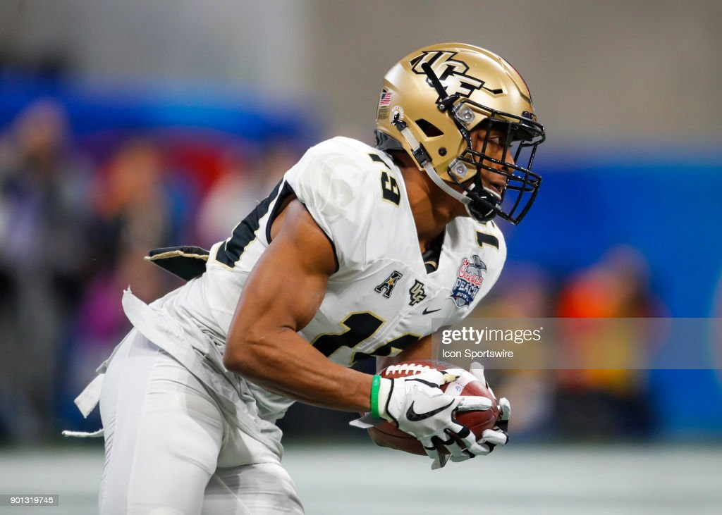 UCF Knights defensive back Mike Hughes (19) returns a kick during the Chick-fil-A Peach Bowl football game of the UCF Knights v Auburn Tigers at Mercedes-Benz Stadium in Atlanta, GA. The UCF Knights won the game 34-27.