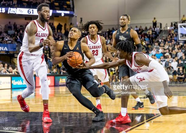 Knights guard BJ Taylor drives between two against the Alabama Crimson Tide players during the basketball game between the UCF Knights and the and...