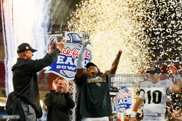 Knights head coach Scott Frost UCF Knights linebacker Shaquem Griffin and UCF Knights quarterback McKenzie Milton celebrate with the trophy at the...