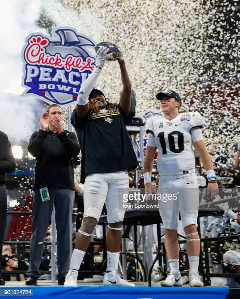 Knights linebacker Shaquem Griffin holds up the Peach Bowl Trophy alongside quarterback McKenzie Milton at the conclusion of the ChickfilA Peach Bowl...
