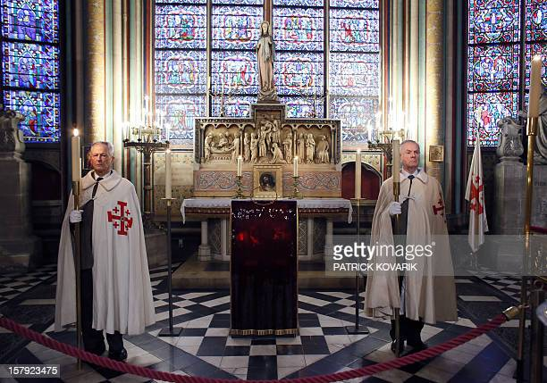 Knights of the order of the Holy Sepulchre stand near the reliquary containing the crown of thorns one of the instruments of Jesus' Passion prior to...