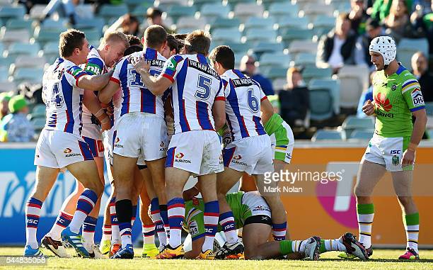 Knights players celebrate a try by Jake Mamo during the round 17 NRL match between the Canberra Raiders and the Newcastle Knights at GIO Stadium on...