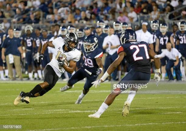 Knights quarterback Quadry Jones attempts to elude two defenders Connecticut Huskies linebacker Omar Fortt and Connecticut Huskies defensive back...