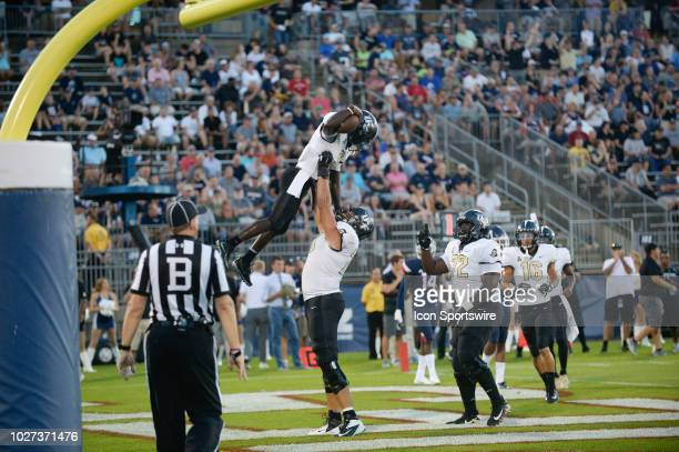 Knights running back Adrian Killins Jr and UCF Knights offensive lineman Wyatt Miller celebrate after a touchdown during the game between the UConn...