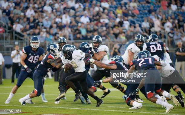 Knights running back Adrian Killins Jr breaks thru the defensive line and gains yards during the game between the UConn Huskies and the UCF Knights...