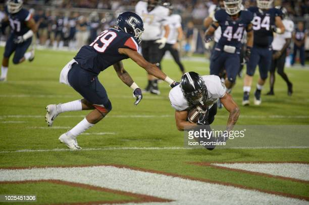 Knights wide receiver Tre Nixon dives into the end zone for a score while Connecticut Huskies defensive back Ryan Carroll defends during the game...