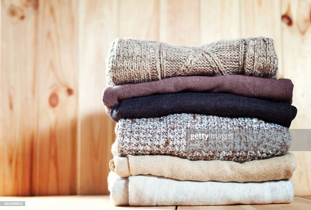Knit cozy sweater folded in a pile on wooden background .Warm the concept : Stock Photo