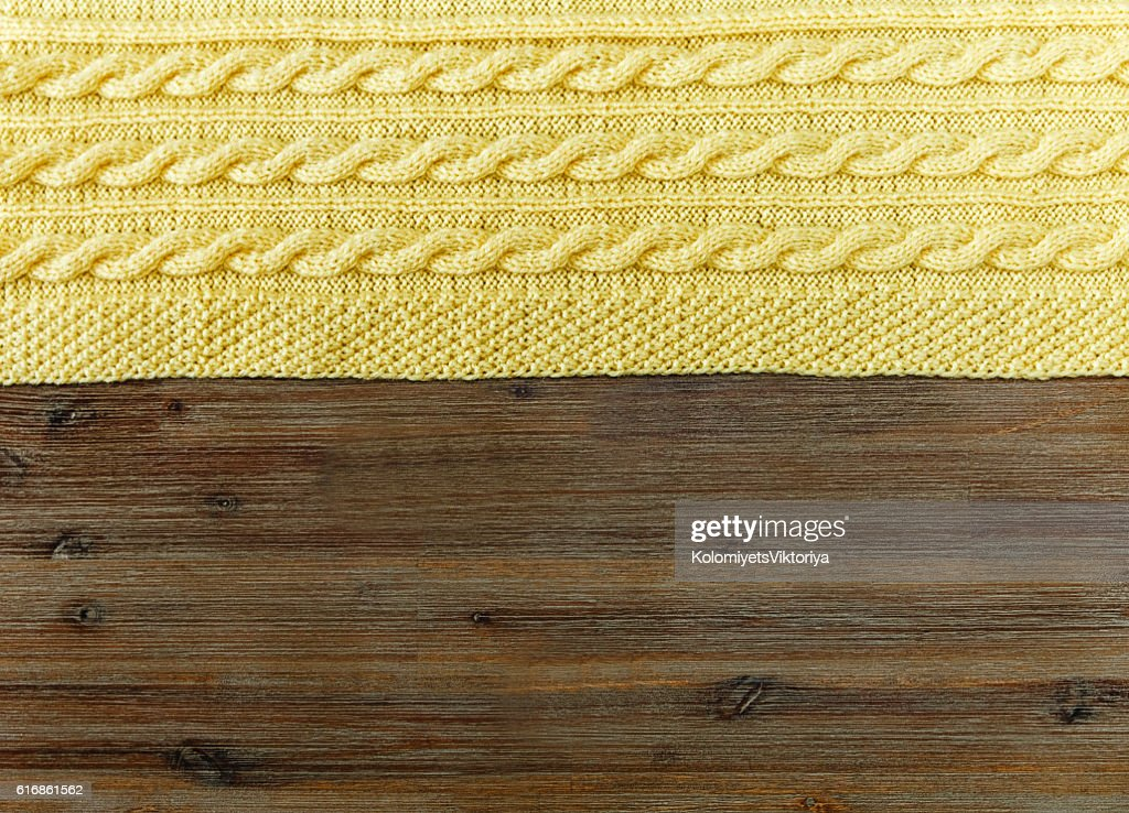 Knited yellow fabric.braid pattern on the wooden background. : Stock Photo