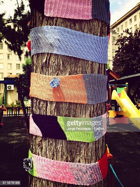 knitted headbands on tree trunk - yarn bombing stock photos and pictures