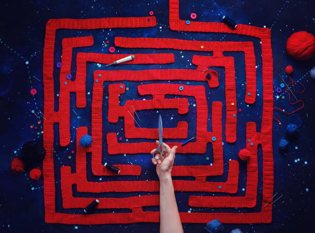 Knitted maze with a hand holding scissors, DIY concept, creative flat lay